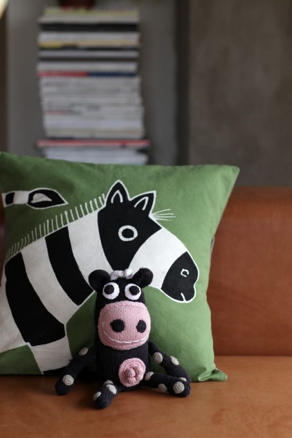 Olive green zebra cushion with knitted cow