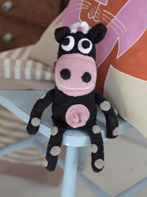 Knitted cow in pastel pink and pastel pink cushion